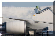 worker of Menzies deicing a JAL 747 airplan